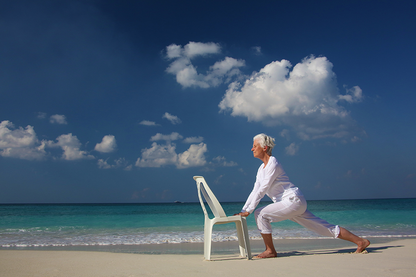 Senior woman doing Yoga with chair on beach